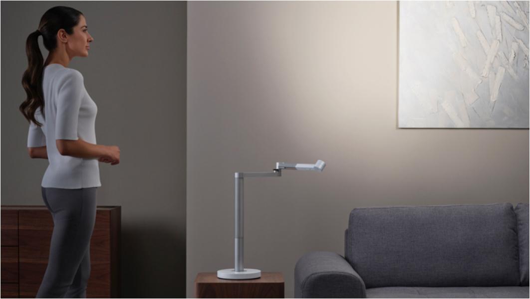 Dyson Lightcycle Morphをスポットライトとして使用し、アート作品を見つめる女性