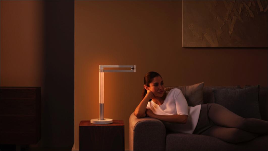 Dyson Lightcycle Morphをアンビエントライトとして使用し、美しいオレンジの光に包まれて女性がくつろいでいる様子